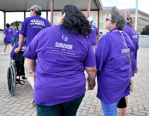 """(Brad Davis/The Register-Herald) Cancer survivors Tammy Brandstetter (5 years), right, and Donna Scullion (4 years) hold hands as they march with fellow survivors and caregivers to the tune of Queen's """"We are the Champions"""" during the opening moments of the Relay for Life of Raleigh County Friday night atop Beckley's Intermodal Gateway."""