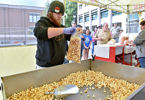 (Brad Davis/The Register-Herald) Appalachian Kettle Corn employee Nick Robinson fills bag after bag with the popular treat as customers keep lining up for more during the Appalachian Block Party, part of the Appalachian Festival Saturday evening in downtown Beckley.