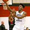 (Brad Davis/The Register-Herald) Greater Beckley Christian's Orlando Potter glides in for a layup as Trinity's Dakota Shepherd defends Saturday afternoon in Prosperity.