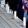 (Brad Davis/The Register-Herald) Nine different colors of beads symbolizing a person's connection to suicide are each palced around a candle during the Walk to Fight Suicide Saturday evening. Purple is for the loss of a relative or friend, gold is for the loss of a parent, silver is for the loss of a first responder or military member, orange is for the loss of a sibling, white is for the loss of a child, red is for the loss of a spouse or partner, green symbolizes personal struggle, teal recognizes the struggles of a loved one and blue is to show support for the cause.
