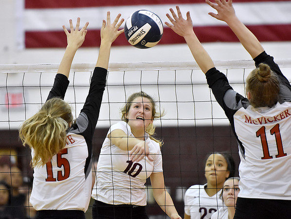 (Brad Davis/The Register-Herald) Woodrow Wilson's Kacee Fansler spikes the ball between St. Albans defenders Karleigh Burdette, left, and Katelyn McVicker during the Class AAA Region 3 championship tournament Saturday evening in Beckley.