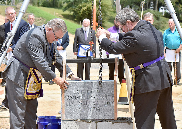 (Brad Davis/The Register-Herald) Masons Rick Nuhfer, right, and Robert Vincent guide a commemorative cornerstone into place as they and other masons from the Grand Lodge of West Virginia and Beckley Lodge 95 take part in a special ceremony at what will be a new Beckley Fire Department location along the bypass across from the main post office Saturday afternoon.