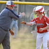 (Brad Davis/The Register-Herald) Independence's Kaylen Parks gets a big high-five from head coach Ken Adkins after ending up at third following a single and a fielder error, part of a late inning rally for the Patriots Thursday evening in Shady Spring.
