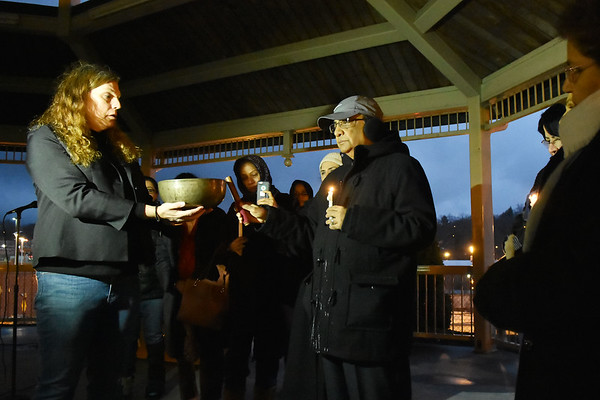 Dr. Ahmed Faheem, right, rings a the bell of remembrance held by Danielle Stewart, left, during a candlelight vigil to honor those killed in Christchurch massacre in New Zealand last week at Word Park in Beckley on Thursday. Around 50 people attended the vent, hosted by the Beckley Human Rights Commission. (Chris Jackson/The Register-Herald)