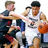 (Brad Davis/The Register-Herald) Greater Beckley Christian's Jay Moore drives along the baseline as Trinity's Briston Bennett defends Saturday afternoon in Prosperity.