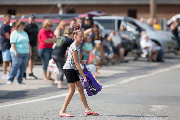 A parade attendant grabs candy during the Labor Day Parade in Pineville on Monday. (Chris Jackson/The Register-Herald)