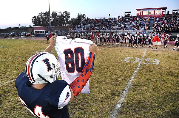Hayden Miller, of Independence, holding up number 80 jersey in support of Roane County High School senior Alex Miller who died last Friday evening while playing a football game at Clay County High School.<br /> (Rick Barbero/The Register-Herald)