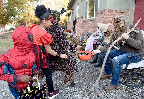 (Brad Davis/The Register-Herald) Costumed visitors (from left) Carmelo Williams, 5, Amelia Lurch, 8, and Aniya Lurch, 10, reluctantly approach for some candy from scary ghoulish creature Derek Tilley, who's actually a nice guy in real life, as they stop by his well-decorated Crescent Road home during Trick or Treat Saturday evening in Beckley.