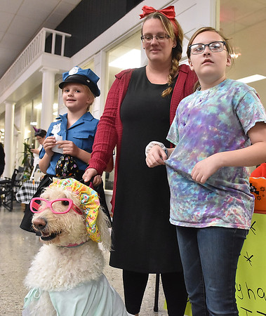 (Brad Davis/The Register-Herald) Amber Rozell, middle, and daughters Allison, left, and Rachael wait patiently for the contest to get underway with their dog Ginger, who is dressed up the Granny from Little Red Riding Hood during the Humane Society of Raleigh County's Howl-o-Ween pet costume contest Saturday afternoon inside the Beckley Plaza Mall.