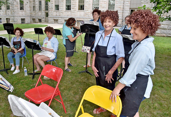 (Brad Davis/The Register-Herald) Enthusiasts Rebecca Nelson, right, and Kathy McGaha, left of Nelson, share a laugh as they and other participants of all ages gather, wigs and all, for a Bob Ross themed pop-up painting workshop put on by 110 Marshall as part of BEX activities around Beckley Saturday afternoon. The wearing of Bob Ross wigs was optional, and were availabale to borrow if attendees didn't already have their own.