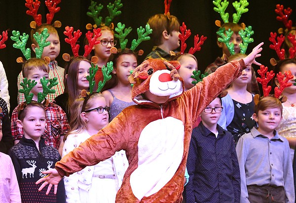 """Jace Canfield, dressed as a reindeer along with the whole third grade class at Maxwell Hill Elementary School, sang """"Blitzen's Boogie and When Santa Claus Gets Your Letter"""" during their annual Christmas performance held at Woodrow Wilson auditorium Monday morning. Music teacher Vickie Pachuta directed each class from pre-k to 5th grade to sing two christmas songs each along with sing alongs from the audience.<br /> (Rick Barbero/The Registewr-Herald)"""