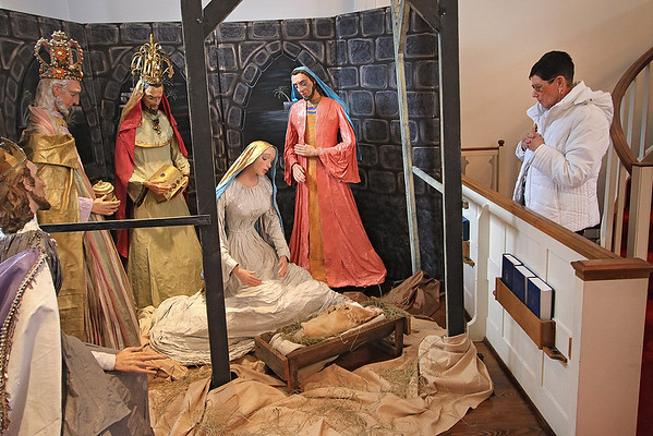 Pam Trail visits a nativity scene created by a local artist more than 60 years ago on display in the sanctuary of Old Stone Presbyterian Church in Lewisburg. (Jenny Harnish/The Register-Herald)