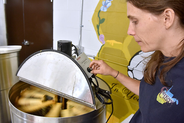 (Brad Davis/The Register-Herald) Lisa Eades, a beekeeper from Summersville's Cheyenne Farm, runs honey-packed combs through the extractor, which does so with an adjustable spin cycle that works in similar fashion to the way a laundry machine spins the water out of wet clothes, during an open house and demo event at Shady Spring High School's new honey extraction facility August 3.
