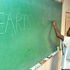 """(Brad Davis/The Register-Herald) Nine-year-old Jahari Keith writes """"Hearts United"""" on the chalkboard as a CPR training course in memory of his late father Brian, who passed away last year due to heart complications, gets underway at the First Baptist Church on Braodway Street in Oak Hill Saturday morning."""