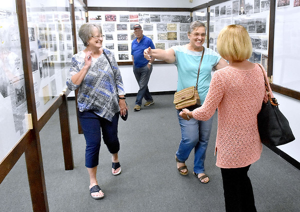 (Brad Davis/The Register-Herald) Lester area natives Sharon Hall, far right, and Kay Denson, 2nd from right, greet one another as friends Lois Trump, far left, and Bill MicMillion, background middle, look on within the displays packed with photos and history of the once booming region inside the newly opened Trap Hill History Museum Friday afternoon inside the former Lester Elementary School, now Lester's City Hall.