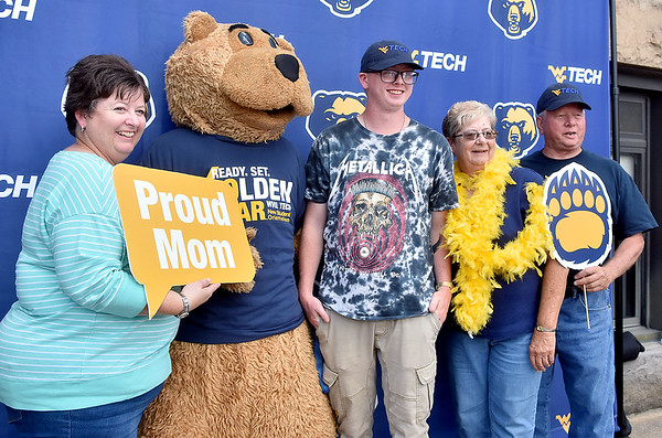 (Brad Davis/The Register-Herald) Wellsburg (Brooke County) native and incoming mechanical engineering student Nathaniel Coursin, middle, is surrounded by mom Amy Hannahs, left, and grandparents Nancy and Bob White as the family gathers around Monty the Golden Bear mascot for a photo at the conclusion of WVU tech's official move-in day and reception Sunday afternoon.