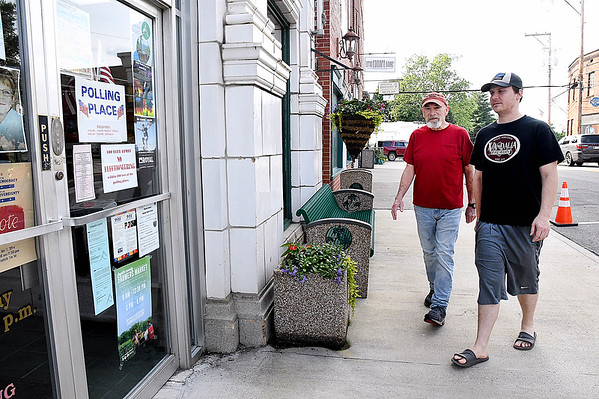 Mack Winters, left, and his son Luke Winters walk to City Hall Tuesday evening on Court Street to cast their vote for the municipal election.<br /> (Rick Barbero/The Register-Herald)