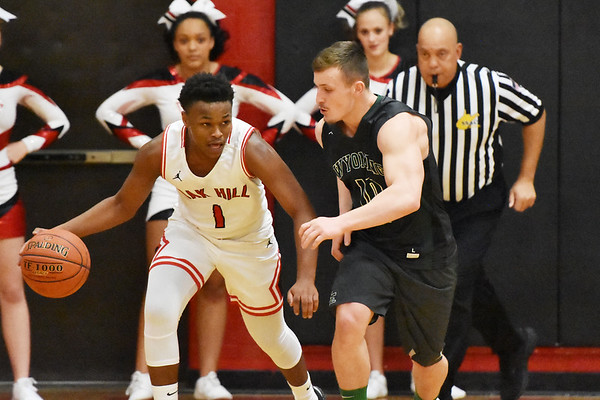 Wyoming East's Chase York (10) defends againts Oak Hill's Jason Manns (1) during the first quarter of their basketball game in Oak Hill on Wednesday. (Chris Jackson/The Register-Herald)