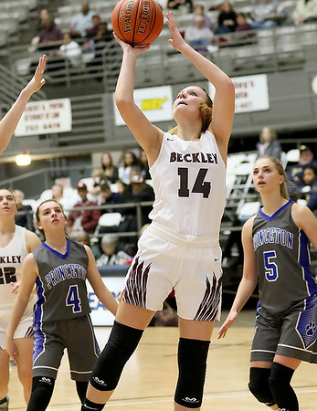 (Brad Davis/The Register-Herald) Woodrow Wilson's Olivia Zolkowski drives to the basket as Princeton's Reagan Southers, left, and Lauren Parish look on Friday night at the Beckley-Raleigh County Convention Center.