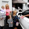 Jenna Roop, left, holds her daughters Charlee, as Mary Roop, Aspen, and Mila Roop, receives a gift from, Bill Roop, right, for Charlee's first birthday held in their driveway off of Grandview Road in Beaver Saturday afternoon because of COVID-19. <br /> (Rick Barbero/The Register-Herald)