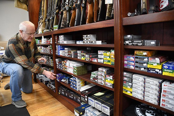 Ron Wood, owner Flat Top Arms in Beckley. grabs a box ammo. Guns and ammo have been on the rise due to the coronavirus. <br /> (Rick Barbero/The Register-Herald)