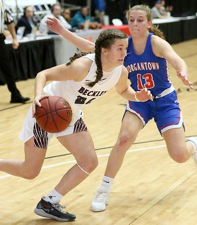 (Brad Davis/The Register-Herald) Woodrow Wilson's Liz Cadle cuts right and drives along the baseline as Morgantown's Cat Wassick defends during Big Atlantic Classic action Thursday night at the Beckley-Raleigh County Convention Center.
