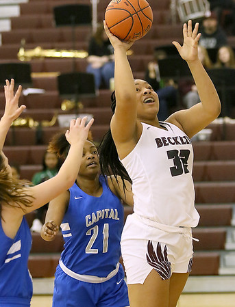 (Brad Davis/The Register-Herald) Woodrow Wilson's Jamara Walton takes a pass underneath and score as Capital's Stephanie Hudnall, left, and Ryuana Calloway defend Wednesday night in Beckley.