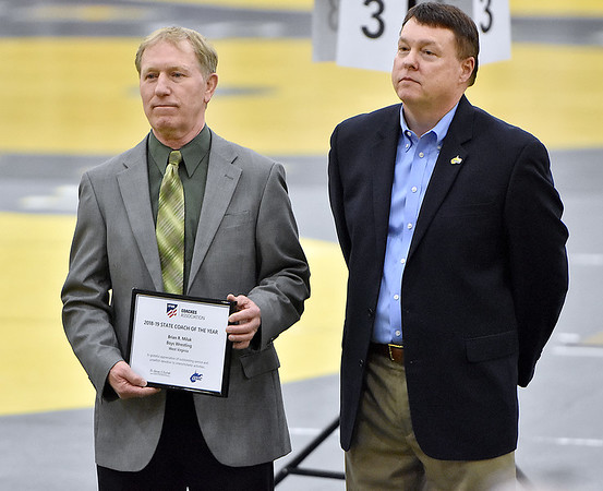 (Brad Davis/The Register-Herald) Greenbrier East head wrestling coach Brian Miluk is honored as the WVSSAC and NFHS Coach of the Year for outstanding service and unselfish devotion to interscholastic activities prior to Friday's night session at the 73rd Annual State Wrestling Tournament in Huntington. WVSSAC's Wayne Ryan looks on at right after publicly recognizing him.