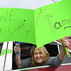 Anita Allen, of Beckley, displays a message as she passes in a parade of cars past Tammy Evans, of Beckley,  home on the corner of, Park Ave. and Third Ave., Family and friends celebrated with a parade of 14 cars and two fire trucks the one year anniversary of her daughter, Shannon Barbero, of Prosperity, donating half her liver to save her mothers life. Evans, who suffered from NASH, nonalcoholic steatohepatitis, stood her distance because of COVID-19, was surprised and said, How many people can say they had their own parade?<br /> (Rick Barbero/The Register-Herald)