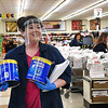 Rhonda Martin shops for one of their customers waiting outside Goodson's Supermarket on Valley Drive in Oceana Wednesday because of the coroanvirus crisis, it caused the Health Department on Tuesday reducing the number shoppers to only10 at a time. Goodson's supplied their employees each with face masks and most chosed to wear them and they also offered to shop for their customers avoiding long wait times to enter the store.<br /> (Rick Barbero/The Register-Herald)