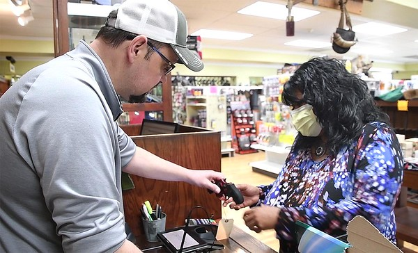 Benny Harper, left, shows Laverne Tyree, of Beckley, a hand gun at Flat Top Arms in Beckley. Sales of ammo and guns have been on the rise due to the coronavirus. <br /> (Rick Barbero/The Register-Herald)