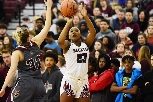 Woodrow Wilson's Victoria Staunton (23) buries a jump-shot over George Washington's Kaya Thompson (32) during their Class AAA, Region Conference Final in Beckley on Tuesday. (Chris Jackson/The Register-Herald)