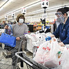 Delores Browning, of Oceana, W.Va. waits for Molly Stanley to bag her groceries at Goodson's Supermarket on Valley Drive in Oceana Wednesday morning and was only one of ten shoppers allowed in the store because the Health Department on Tuesday reduced the number shoppers to only10 at a time. Goodson's supplied their employees each with face masks and most chosed to wear them and they also offered to shop for their customers avoiding long wait times to enter the store.<br /> (Rick Barbero/The Register-Herald)