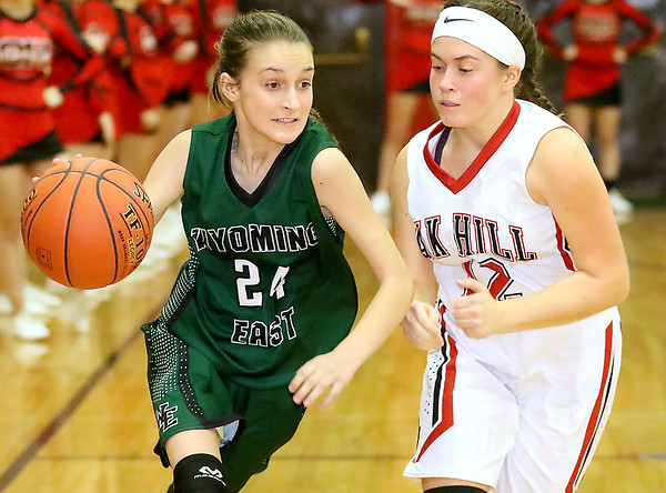 (Brad Davis/The Register-Herald) Wyoming East's Laken Toler drives up the court as Oak Hill's Chelsea Pack defends Thursday night in Oak Hill.