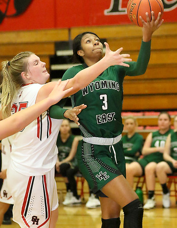 (Brad Davis/The Register-Herald) Wyoming East's Daisha Summers drives and scores as Oak Hill's Savannah Holbrook defends Thursday night in Oak Hill.