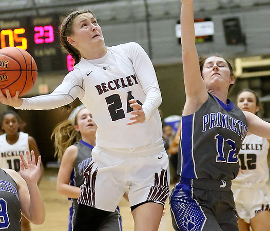 (Brad Davis/The Register-Herald) Woodrow Wilson's Liz Cadle drives to the basket as Princeton's Laken Dye defends Friday night at the Beckley-Raleigh County Convention Center.