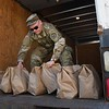 Charles Markley, W.Va. National Guard 115th Clarksburg unit, loading bags of meals prepared by Tamarack in Beckley Monday morning. Tamarack joined together with Raleigh County and Monroe schools to provide two meals a day for five day to 1500 students from each county. 1500 meals were delivered to Monroe County Monday morning and additional 1500 meals will be prepared and delivered in Raleigh by the W.Va. National Guard to help continue feeding students during the coroanvirus crisis.<br /> (Rick Barbero/The Register-Herald)