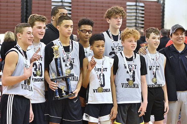 (Brad Davis/The Register-Herald) The WV Wildcats pose with the trophy for attending family members after defeating Southern West Virginia Hustle for the Roundball Classic 7th Grade Championship Sunday morning at Woodrow Wilson High School.