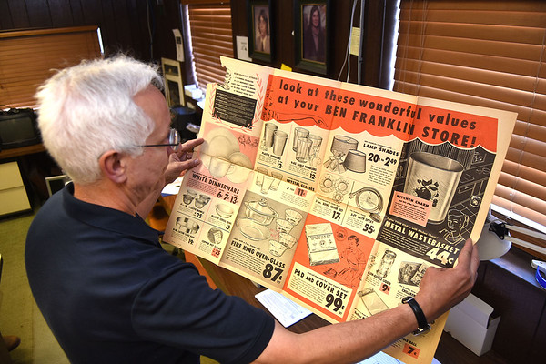 Mike Rahall, owner of the Ben Franklin store in Fayetteville, looks over an 1955 advertisement from the store.<br /> Rick Barbero/The Register-Herald)