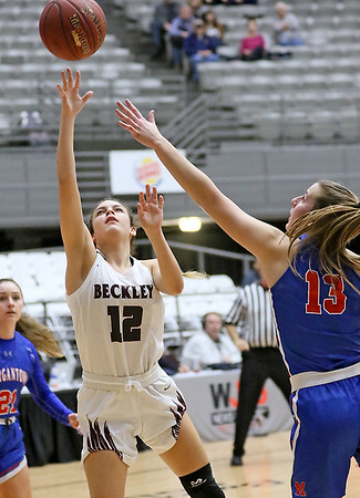 (Brad Davis/The Register-Herald) Woodrow Wilson's Cloey Frantz drives and scores as Morgantown's Cat Wassick defends during Big Atlantic Classic action Thursday night at the Beckley-Raleigh County Convention Center.
