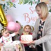 Jenna Roop, right, holds up her daughters, Charlee's, left, first bithday cake for a drive-through party held because of COVID-19 in their driveway off of Grandview Road in Beaver Saturday afternoon. Also pictured, Mila Roop, 6, sister.<br /> (Rick Barbero/The Register-Herald)