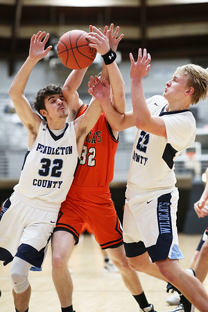 Summers County's Hunter Thomas (32) goes for a rebound as Pendelton County's Cole Day (32) and Tanner Townesend do the same during the first half of their Big Atlantic Classic basketball game  in Beckley on Tuesday. (Chris Jackson/The Register-Herald)