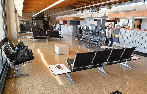 Roy Meadows, mail carrier, walks through the empty terminal at the Raleigh County County Airport Monday. Flight landed from Charlotte with no one boarding the plane.<br /> (Rick Barbero/The Register-Herald)