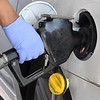 Customer using precautions preparing to pump gas with a rubber gloves at the Sheets Station on Neville Street in Beckley.<br /> (Rick Barbero/The Register-Herald)
