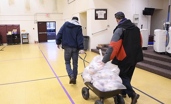 Scott Whitt, left and Acie Toler, Raleigh County bus drivers, wheel out lunches in the gym at Crescent Elementary School to be delivered to Raleigh County students due to the coronavirus crisis.<br /> (Rick Barbero/The Register-Herald)