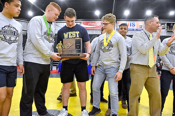 (Brad Davis/The Register-Herald) Greenbrier West grapplers claim their trophy after winning a second straight Class A State Championship Saturday night at the 73rd Annual State Wrestling Tournament in Huntington.