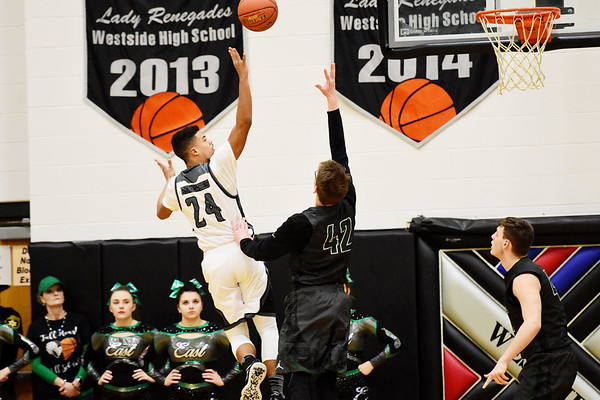 Westside's Jace Colucci (24) puts a shot up over Wyoming East's Anthony Martin (42) during the first half of their basketball game in Clear Fork on Tuesday. (Chris Jackson/The Register-Herald)