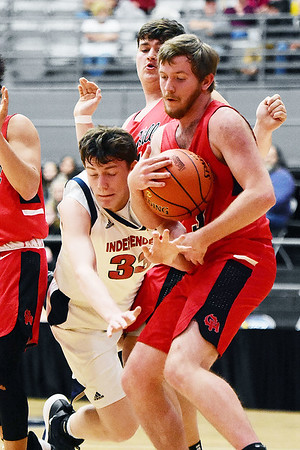 Oak Hill's Hunter Rinehart (20) takes the ball from Independence's Zach Bolen (33) during the first half of their Class AA Region 3, Section 1 tournament basketball game in Beckley on Tuesday. (Chris Jackson/The Register-Herald)