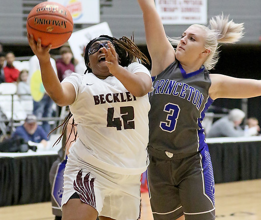 (Brad Davis/The Register-Herald) Woodrow Wilson's Adriana Law drives and scores as Princeton's Taylor Scott defends Friday night at the Beckley-Raleigh County Convention Center.