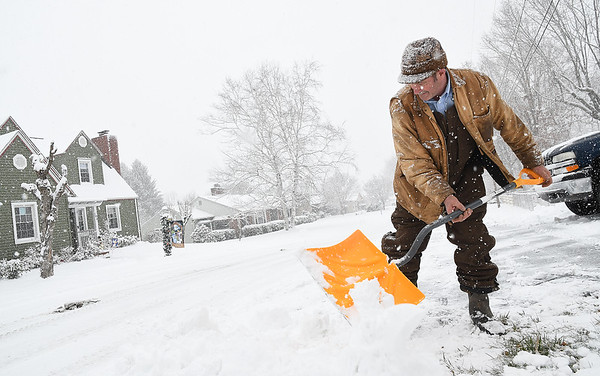 Ron Shuck cleaning snow off his sidewalk on Foote Street in Beckly Tuesday morning.<br /> (Rick Barbero/The Register-Herald)